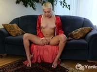Lily Lennox sits on the couch and spreads her tight legs.