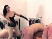 BDSM mistress flogging her masochistic subs