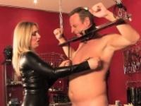 Latex mistress flogging a ball gagged sub