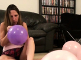 Good looking brunette blowing balloons