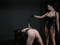 Busty mistress flogging bound slave in dungeon