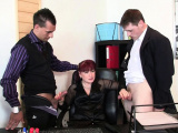 Redhead business lady swallows two big cocks at once